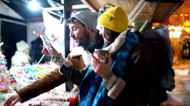 att köpa lite godis på julmarknad. - spendera pengar bildbanksvideor och videomaterial från bakom kulisserna