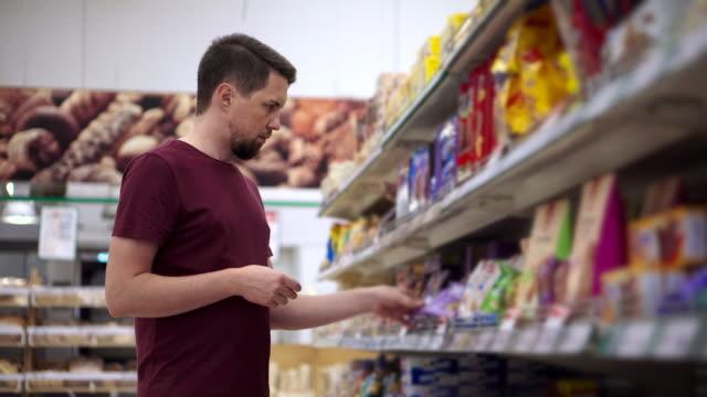 vídeos y material grabado en eventos de stock de comprar dulces en el supermercado - galleta dulces