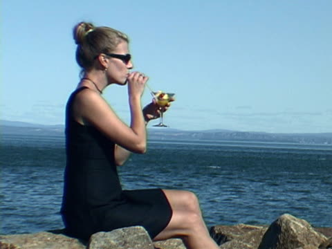 By the Sea NTSC video of a woman dressed up in a black dress having a fancy drink by the seaside and raising her glass at you. As always, there is plenty of space in this video to ad your own text. one mid adult woman only stock videos & royalty-free footage