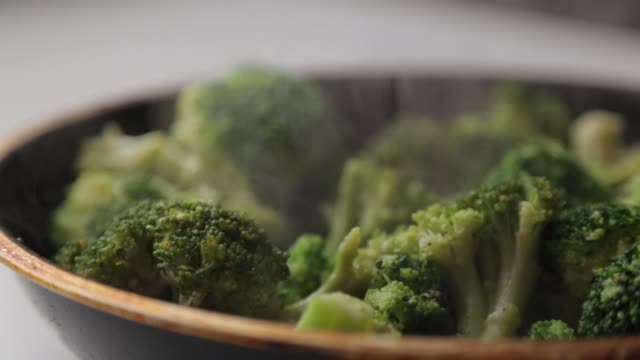 cabbage broccoli in a pan with oil and spices. steam and smoke from cooking fresh green cabbage. - broccolo video stock e b–roll
