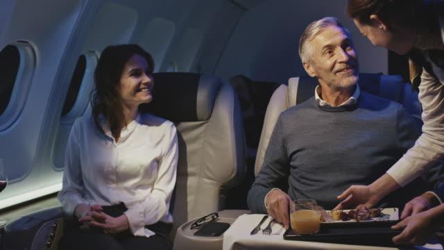 vídeos y material grabado en eventos de stock de tripulación de cabina dando cena al hombre de negocios - viaje en primera clase