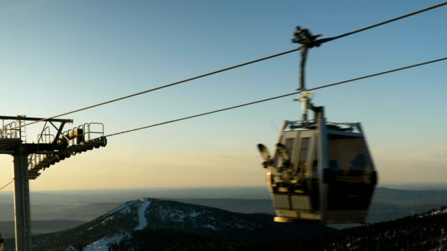 cabin of poma lift with snowboarders moves against mountain