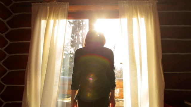 Cabin Retreat - Young woman in front of the window raising her hands. video