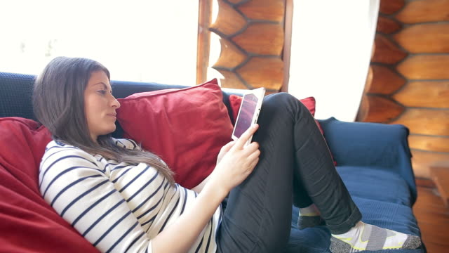Cabin Retreat - Young woman using digital tablet in the log cabin. video