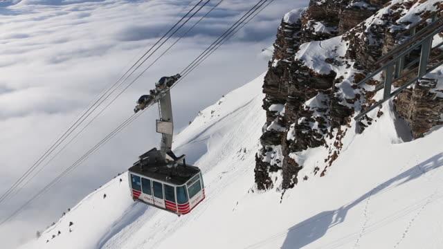 vídeos de stock e filmes b-roll de cablecar ascends from valley bottom, winter snow - suíça