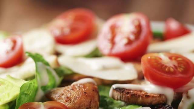 caesar salad with cherry tomatoes on wooden table caesar salad with cherry tomatoes on wooden table, closeup photo salad bowl stock videos & royalty-free footage