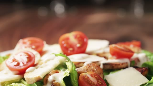 caesar salad with cherry tomatoes on wooden table caesar salad with cherry tomatoes on wooden table, homemade dish salad bowl stock videos & royalty-free footage