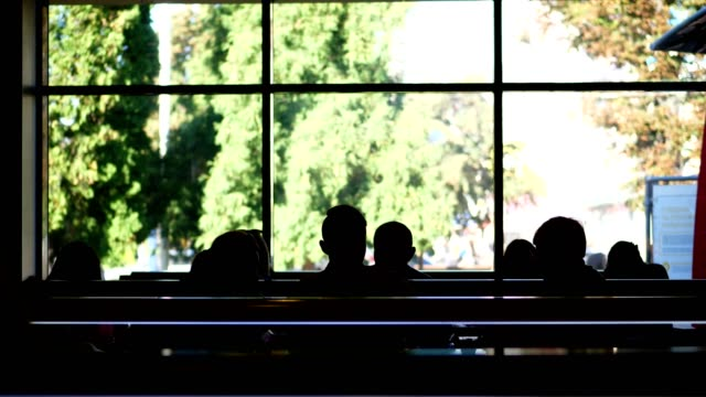 cafe, cafeteria, catering establishment. many dark silhouettes of people on the background of a large window. people having lunch inside a modern restaurant with big windows