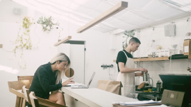 vídeos de stock e filmes b-roll de cafe manager and barista working at the restaurant - avental