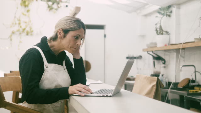 vidéos et rushes de gestionnaire de café utilisant le dessus de tour derrière le compteur - une seule femme d'âge mûr