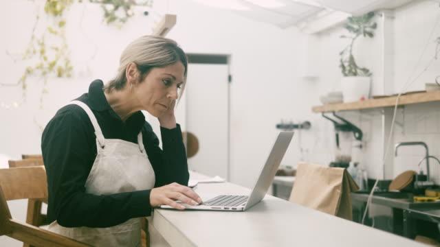 vídeos de stock e filmes b-roll de cafe manager using lap top behind the counter - avental