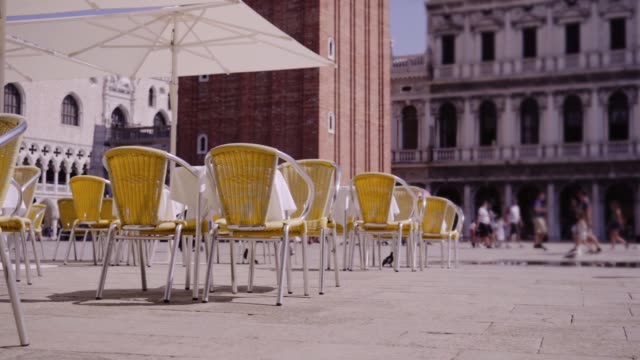 cafeteria with tables and umbrellas near ancient building