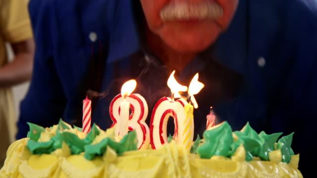 vídeos de stock, filmes e b-roll de bolo e velas de sopro do homem sênior na festa de anos - assistência à terceira idade
