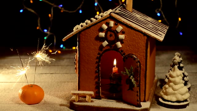 Cake in the shape of houses, sweets and lit sparklers video