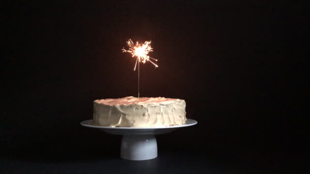 Cake with sparkler on black background Cake with sparkler on black background happy birthday stock videos & royalty-free footage