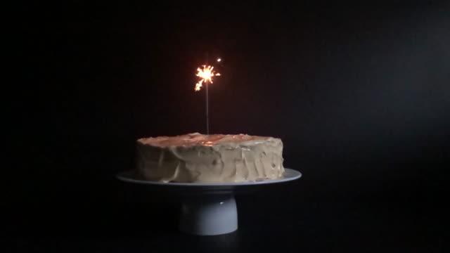 kuchen mit wunderkerze auf schwarzem hintergrund - geburtstagstorte stock-videos und b-roll-filmmaterial