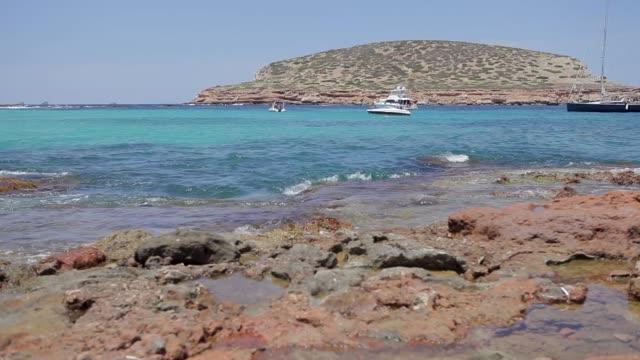 cala conta ibiza beach, beach with boat in the background, the beautiful island - formaggio comté video stock e b–roll