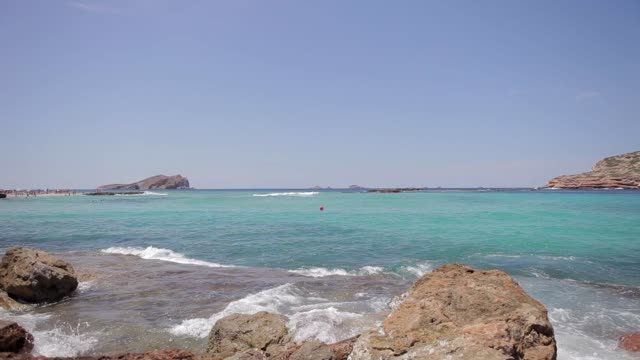 cala conta ibiza beach, image at ground level in a cove of ibiza turquoise waters and waves crashing with wet rocks - formaggio comté video stock e b–roll