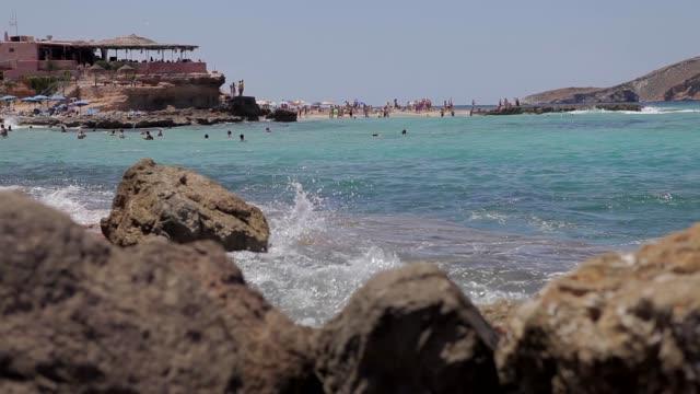cala conta ibiza beach, people bathing in the beaches of ibiza - formaggio comté video stock e b–roll