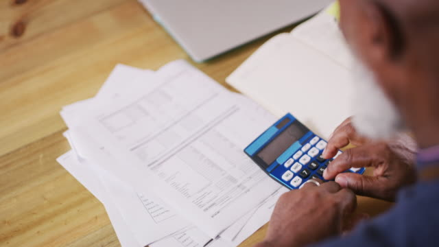 Calculating his spendings for the month 4k video footage of a man using a calculator while doing paperwork at home debt stock videos & royalty-free footage