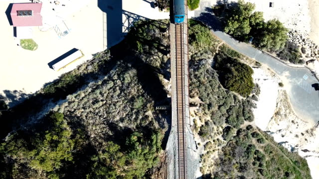 vídeos de stock e filmes b-roll de california coastline with mountains and train going by on tracks - estrada 001