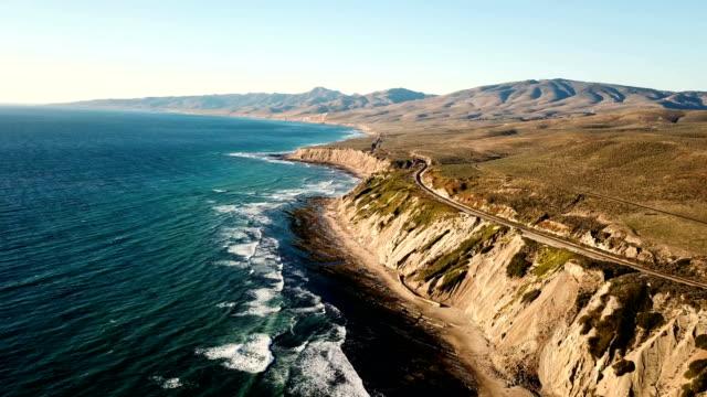 vídeos de stock e filmes b-roll de california coastline with mountains and train tracks from above - califórnia
