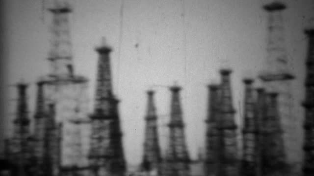 1938: California oil drilling fields steel derrick tower rigging. video