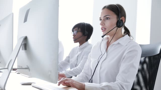 Call Center Agents Consulting Clients On Hotline At Office Call Center Agents Consulting Clients On Hotline At Office. Woman Operator In Headset Working At Support On Computer garnish stock videos & royalty-free footage