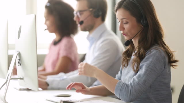 Call center employee girl provide professional support to customer Service phone operators sit at shared desk focus on sales agent woman in headset use pc answers incoming calls talk with client provide professional support to customers sell company product concept call center stock videos & royalty-free footage