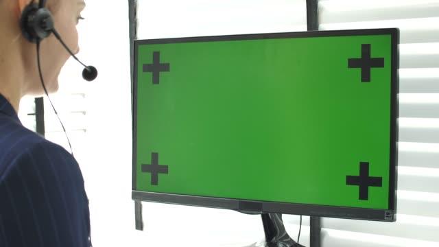 call center rozmawia ze swoim klientem i za pomocą komputera zielony ekran - słuchawki filmów i materiałów b-roll