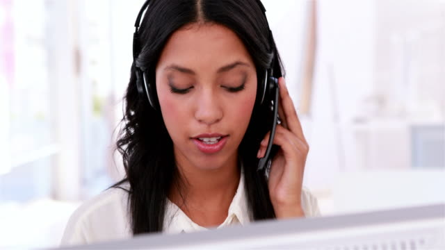 Call centre agent working and talking on headset video