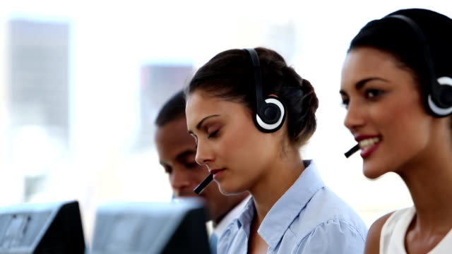 Call centre agents working in their office Call centre agents working in their bright office call centre videos stock videos & royalty-free footage