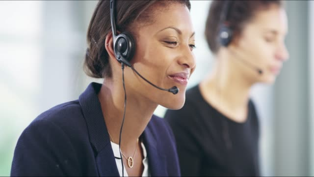 Call us when you need a hand 4k video footage of an attractive young female callcenter agent working on a desktop in her office with a colleague in the background call centre videos stock videos & royalty-free footage