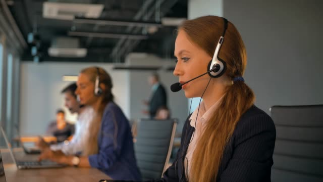 Call-center employees work in deal office Call-center employees work in deal office. Young handsome female in headset on first plan talking with customer. Modern business room with beautiful view. 4k UltraHD. call centre videos stock videos & royalty-free footage
