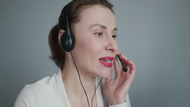 Call-centre lady employee happy of conversation with customer calling by headset answering questions on line, nice polite call center agent wearing headphones talking to client in office