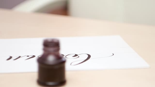 Calligraphic tools on beige table. Close shot. Side view. Camera moves along the desk with open inkpot and brush pen.