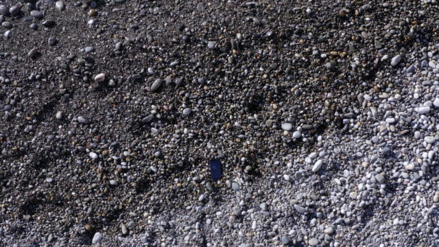 vídeos de stock e filmes b-roll de calling mobile phone lying on pebble beach at sea shore view from flying drone. aerial view smartphone on stones and water waves on sea beach - phone, travelling, copy space