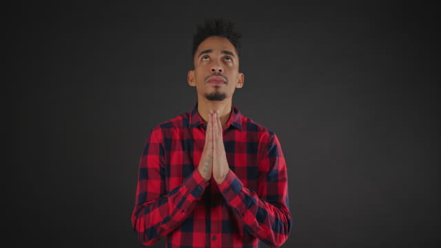 A calm african man in shirt is doing a pray gesture with his hands isolated on dark background