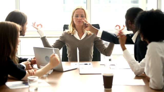 calm businesswoman meditating at meeting with multiracial colleagues, no stress - stress emotivo video stock e b–roll