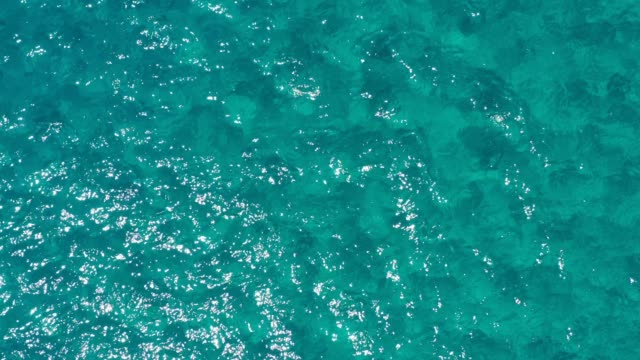 Calm Clear Sea Water Background. Calm Sea Water Background. Aerial footage of a perfectly crystal clear blue turquoise water. Top view of crystal clear blue water surface.