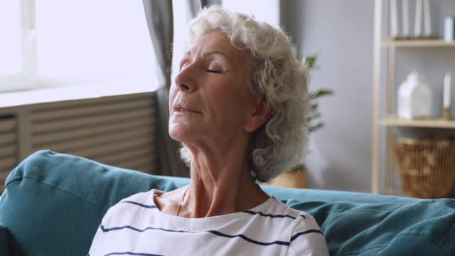 ruhige ältere alte dame entspannende atmen frische luft auf dem sofa - atemübung stock-videos und b-roll-filmmaterial