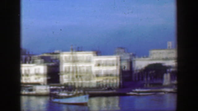 1953: calm glassy waters on urban bayside waters classic buildings community. - portorico video stock e b–roll