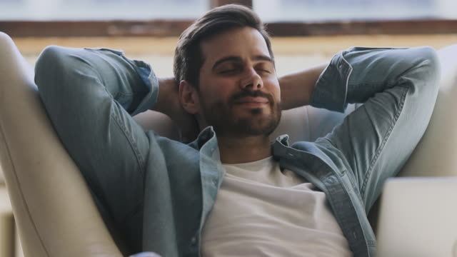 calmo felice giovane sano appoggiato respirando su comoda poltrona - sonnecchiare video stock e b–roll