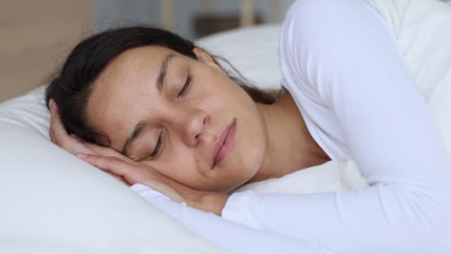 vidéos et rushes de visage serein calme de jeune femme de jeune femme dormant bien dans le lit - expression positive