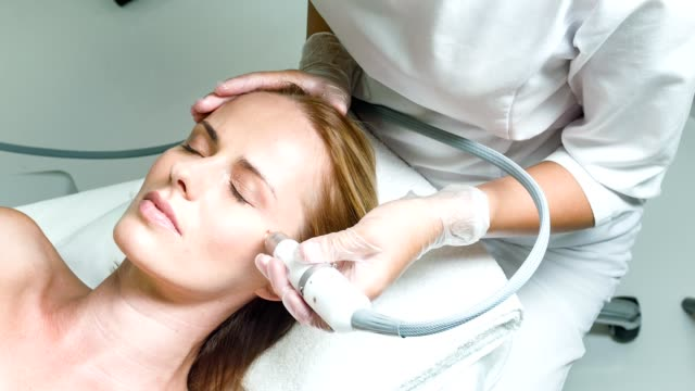 calm lady having facial skin rejuvenation procedure - skin care stock videos & royalty-free footage