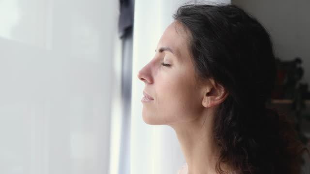 vídeos y material grabado en eventos de stock de señora tranquila tomando aliento profundo de aire fresco en la ventana - descansar