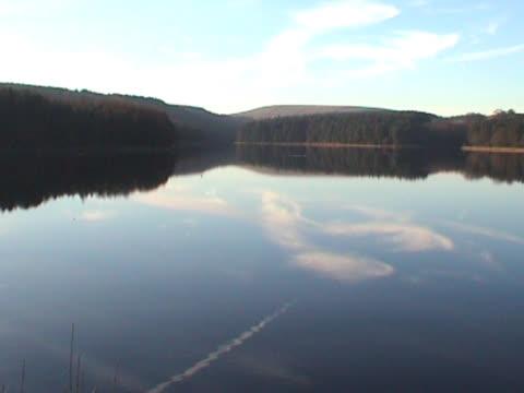 lago calmo, che riflette il cielo azzurro, nuvole e vapore trail - pinacee video stock e b–roll