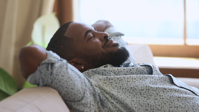 Calm lazy african man napping breathing fresh air on sofa