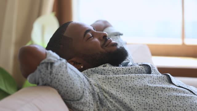 sakin tembel afrikalı adam kanepede temiz hava soluma uyuklama - sessizlik stok videoları ve detay görüntü çekimi