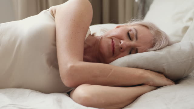 Calm peaceful happy adult older woman sleeping at home. Tranquil middle aged granny lying on side in bed, enjoying sweet night dreams. Calm peaceful happy adult older woman relaxing on comfortable soft pillow orthopedic mattress, sleeping at home or hotel. deep stock videos & royalty-free footage